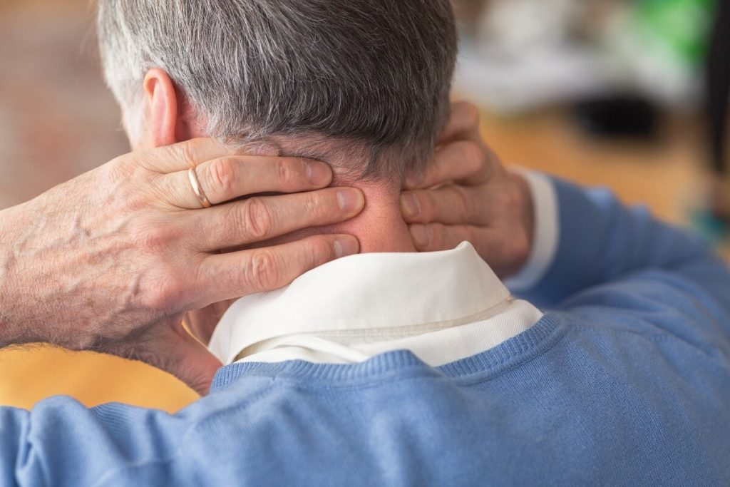 elderly-man-having-neck-pain-sitting-on-sofa-rear