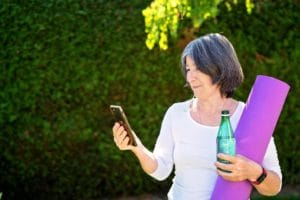 Mature adult woman practicing fitness outdoors holding bottle of water and yoga mat looking at online guide at smartphone
