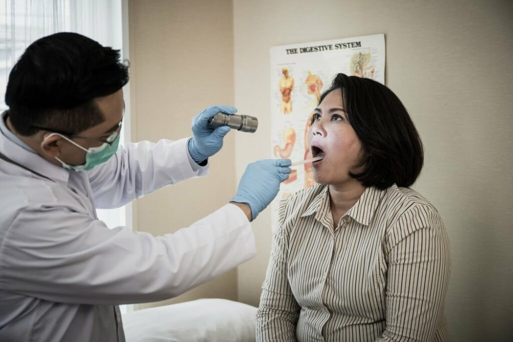doctor in white uniform gown checkup patient's mouth with flashlight Physician check up